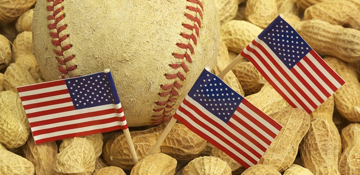 Studio shot of a well-used baseball and miniature flags on a bed of peanuts. Concept for baseball games, ballpark snacks, or Fourth of July.
